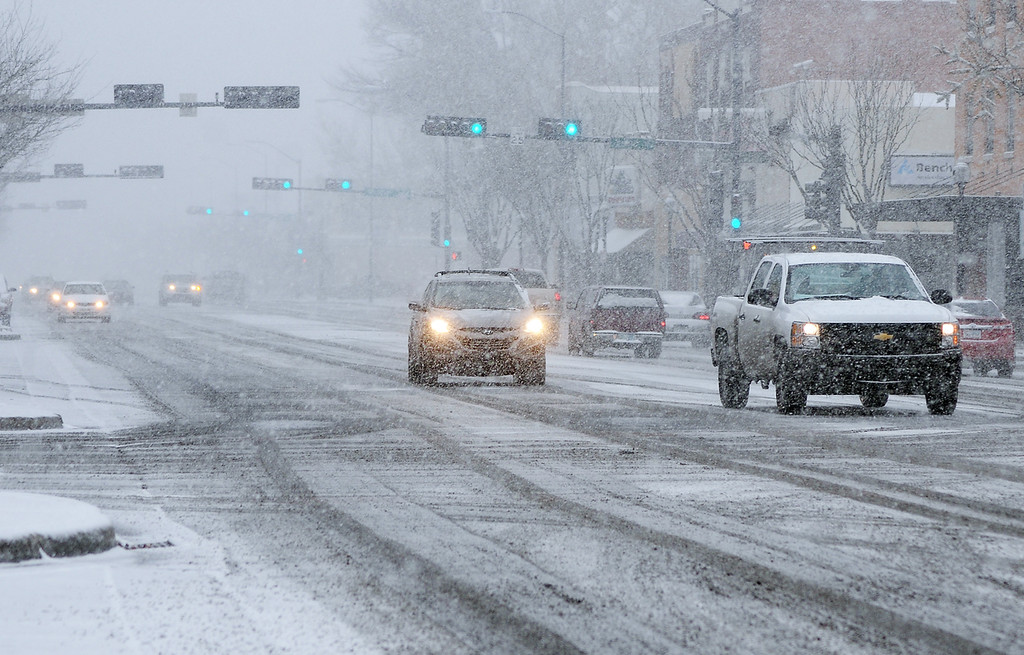 . In this photo taken Thursday, Dec. 5, 2013, motorists proceed cautiously along Main Street as snow falls in downtown Roswell, N.M. (AP Photo/Roswell Daily Record, Mark Wilson)