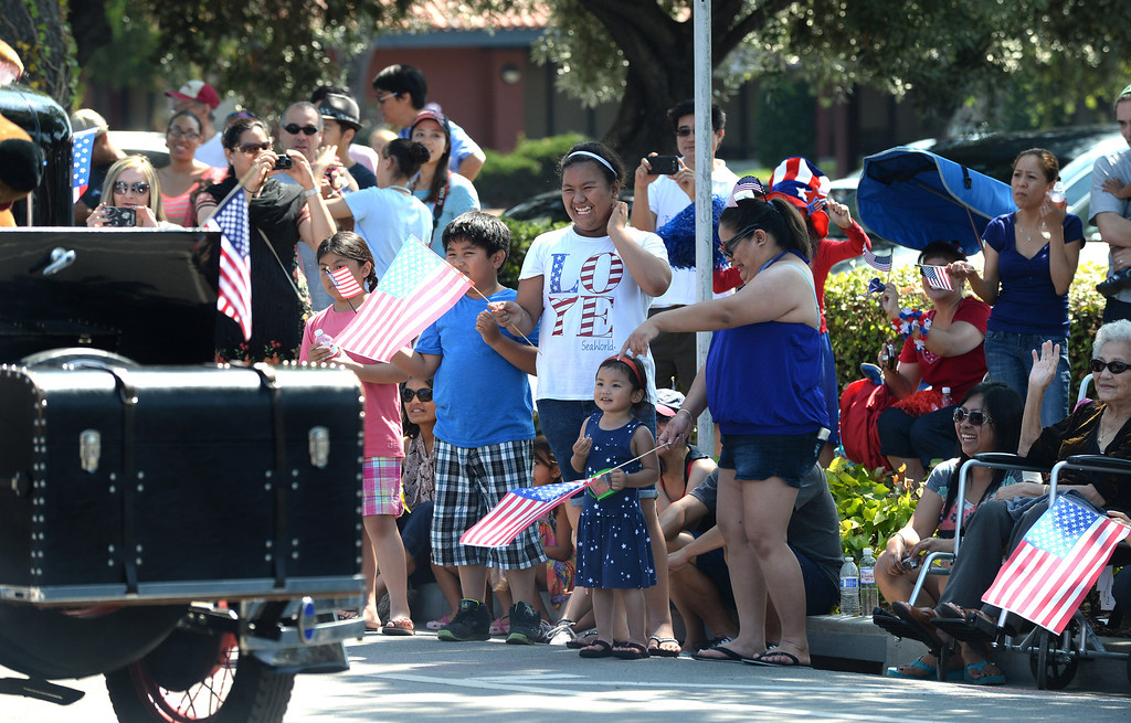 . People wave as participants pass by during the Fourth of July parade in Fremont, Calif., on Thursday, July 4, 2013. The parade featured more than 70 entries. (Dan Honda/Bay Area News Group)