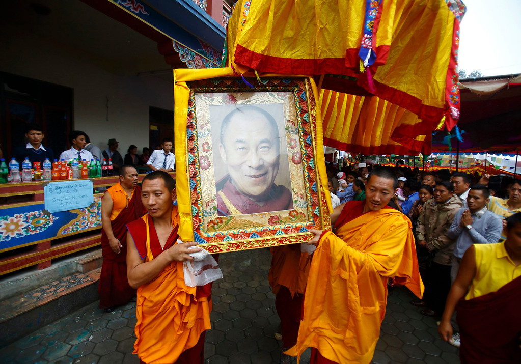 . Tibetan monks carry the portrait of exiled spiritual leader Dalai Lama during celebrations of the 78th birthday of Dalai Lama in Kathmandu July 6, 2013. During last month\'s visit of Chinese State Councilor Yang Jiechi, Chairman of the Interim Election Council Khil Raj Regmi said Nepal is firmly committed to the One-China Policy and reaffirmed its stand that the territory of Nepal will not be allowed to be used for any activities against China. Nepal ceased issuing refugee papers to Tibetans in 1989 and recognizes Tibet to be a part of China. REUTERS/Navesh Chitrakar
