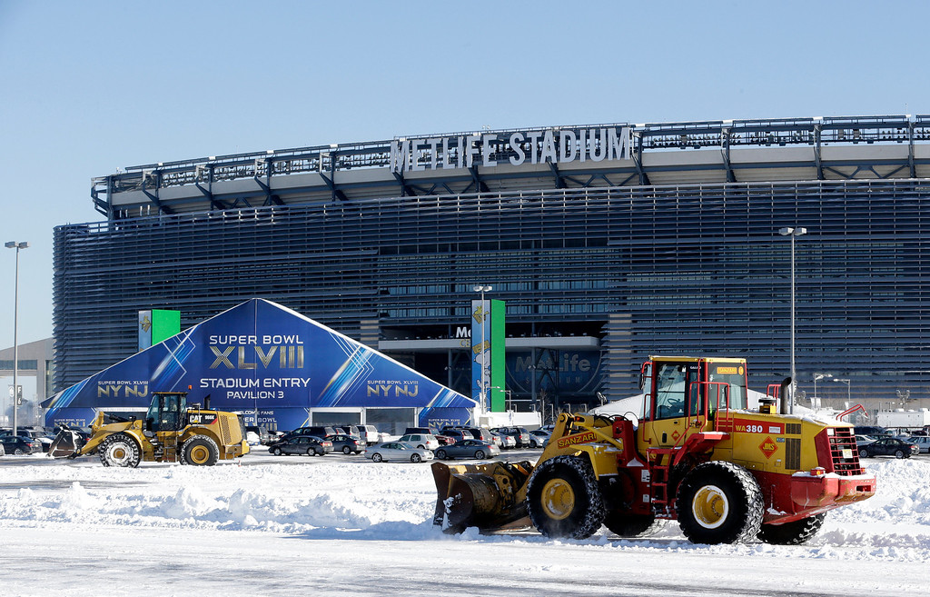 . Tractors plow snow off the parking lot of MetLife Stadium near a tent which will serve as an access point into Super Bowl XLVIII as crews removed snow following a snow storm, Wednesday, Jan. 22, 2014, in East Rutherford, N.J.   (AP Photo/Julio Cortez)