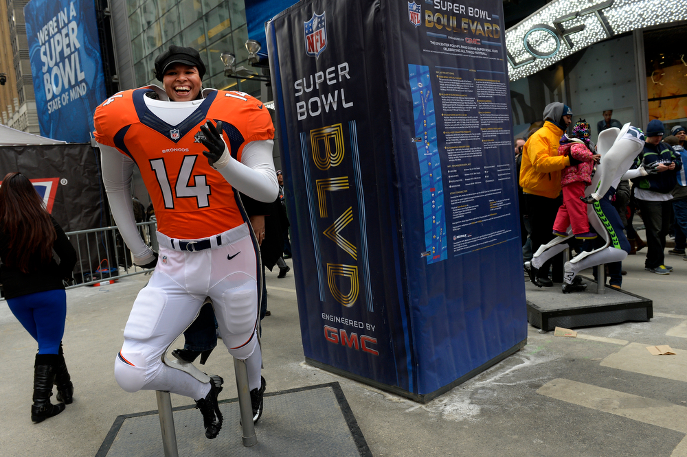 Description of . Broncos fan Yariza Rodriguez, of the Bronx, has her picture made with a broncos uniform  while visiting Times Square in New York, NY January 31, 2014. The NFL has transformed 13 blocks of Broadway into Super Bowl Boulevard before Sundays Super Bowl between the Denver Broncos and Seattle Seahawks. She predicts a 24-17 Broncos victory.   (Photo By Craig F. Walker / The Denver Post)
