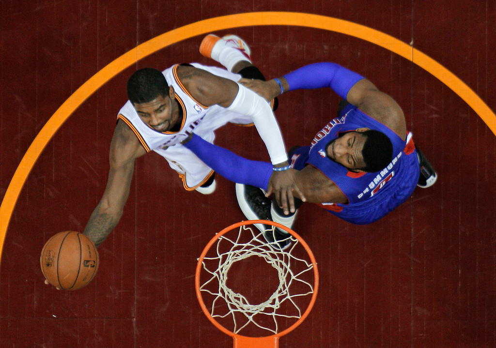 . Cleveland Cavaliers\' Kyrie Irving, left, shoots against Detroit Pistons\' Andre Drummond during the first quarter of an NBA basketball game Monday, Dec. 23, 2013, in Cleveland. (AP Photo/Mark Duncan)