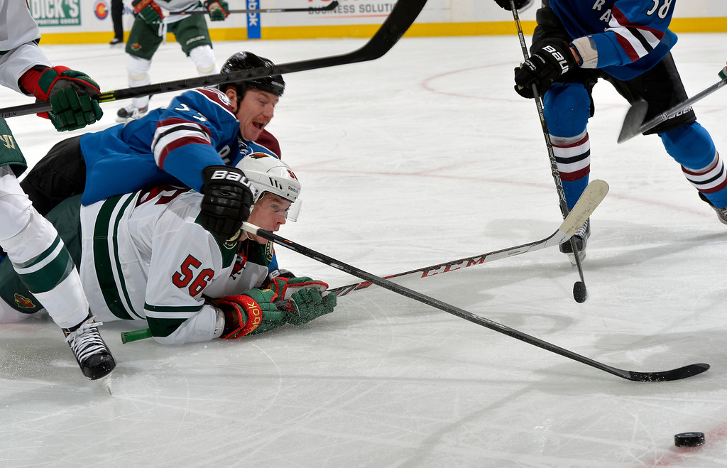 . Colorado Avalanche left wing Cody McLeod (55) and Minnesota Wild left wing Erik Haula (56), from Finland, go after the puck during the first period of an NHL hockey game  onSaturday, Nov. 30, 2013, in Denver. (AP Photo/Jack Dempsey)