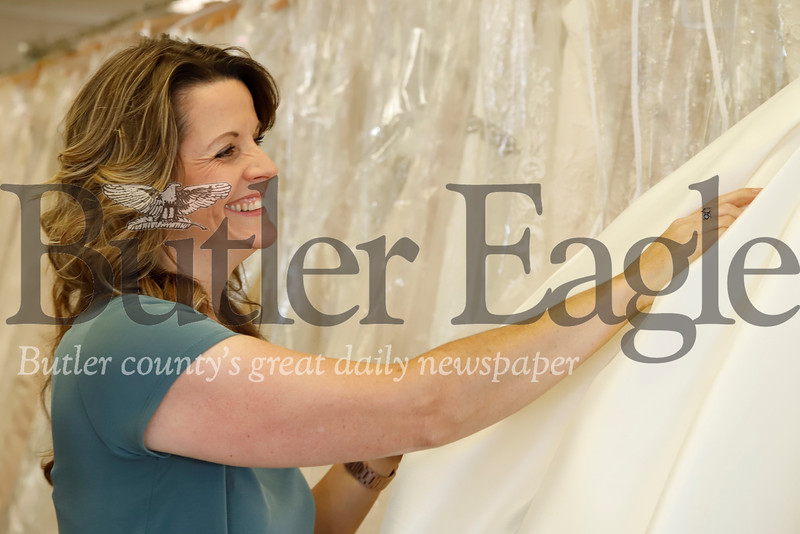 D.I. Bridal Boutique of Butler store owner Cindy Ciccozzi, pulls out a sample wedding gown off the rack to show popular features brides-to-be look for in their dresses. Seb Foltz/Butler Eagle