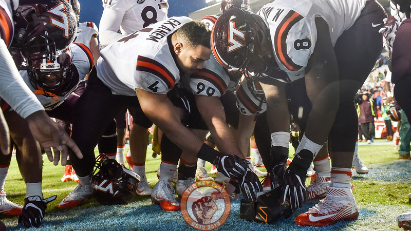 Virginia Tech defensive tackle Nigel Williams (8) and teammates Ken Ekanem (4) and defensive lineman Vinny Mihota (99) tear off small pieces of carolina blue turf and place them in the lunch pail. (Michael Shroyer/ TheKeyPlay.com)