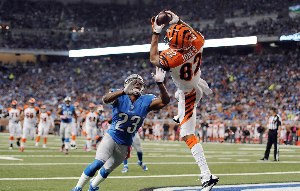 . Cincinnati Bengals\' Marvin Jones (82) catches a 12-yard touchdown reception as Detroit Lions\' Chris Houston (23) defends in the second quarter of an NFL football game on Sunday, Oct. 20, 2013, in Detroit. (AP Photo/Jose Juarez)
