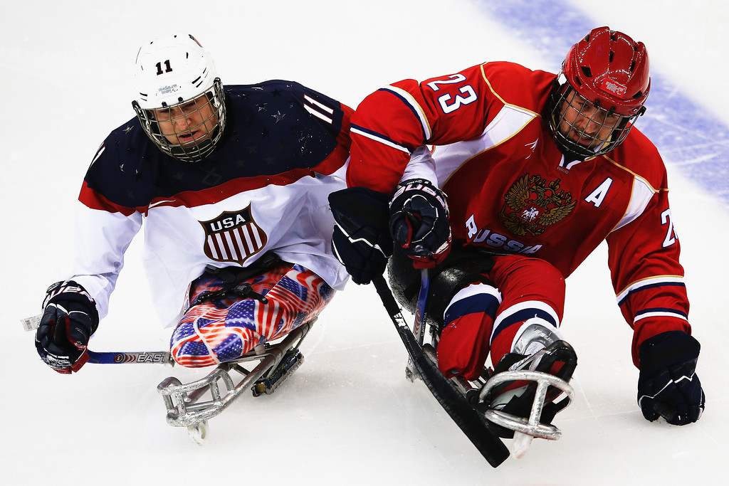 . Tyler Carron of the USA competes with Ilia Volkov of Russia during the ice sledge hockey gold medal game between the Russian Federation and the United States of America at the Shayba Arena during day eight of the 2014 Paralympic Winter Games on March 15, 2014 in Sochi, Russia.