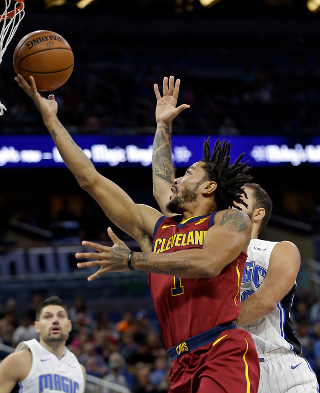 . Cleveland Cavaliers\' Derrick Rose (1) shoots as he gets past Orlando Magic\'s Evan Fournier, right, during the first half of an NBA preseason basketball game, Friday, Oct. 13, 2017, in Orlando, Fla. (AP Photo/John Raoux)
