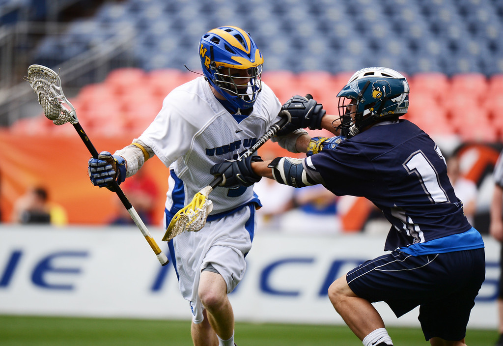 . DENVER, CO. - MAY 18 : Jacob Gladfelter of Wheat Ridge High School (5) , left, controls the ball under the pressure of Ben Brown of Air Academy High School (11) during 4A Boy\'s Lacrosse Championship game at Sports Authority Field at Mile High Stadium. Denver, Colorado. May 18, 2013. (Photo By Hyoung Chang/The Denver Post)