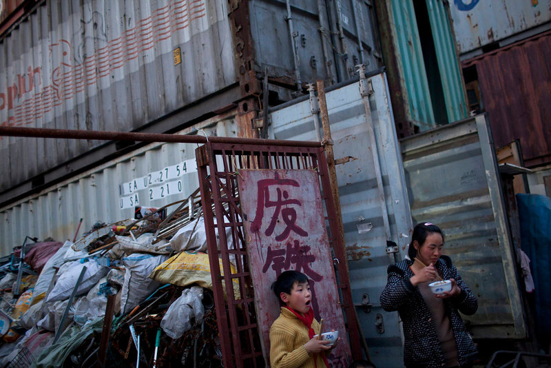 ". A mother and her child eat dinner outside shipping containers which serve as their accommodation, in Shanghai March 4, 2013. The containers, which house different families, were set up by the landlord, who charges a rent of 500 yuan ($ 80) per month for each container. The words on the gate read as ""scrap metal recovery\"". REUTERS/Aly Song"