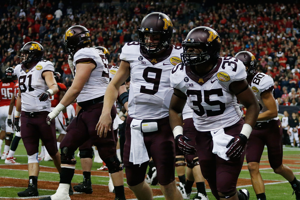 Description of . Phillip Nelson #9 and Rodrick Williams Jr. #35 of Minnesota celebrate a touchdown against Texas Tech during the Meineke Car Care of Texas Bowl at Reliant Stadium on December 28, 2012 in Houston, Texas.  (Photo by Scott Halleran/Getty Images)