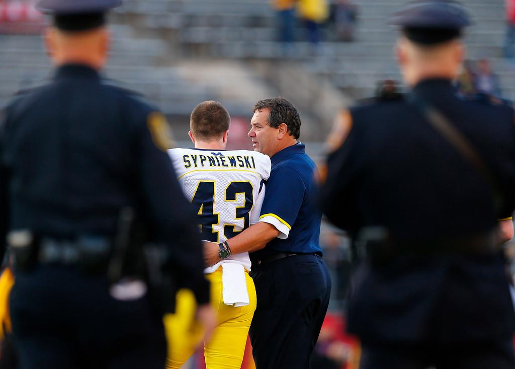 . Michigan coach Brady Hoke talks with Scott Sypniewski as Michigan prepares for an NCAA college football game against Rutgers on Saturday, Oct. 4, 2014, in Piscataway, N.J. (AP Photo/Rich Schultz)
