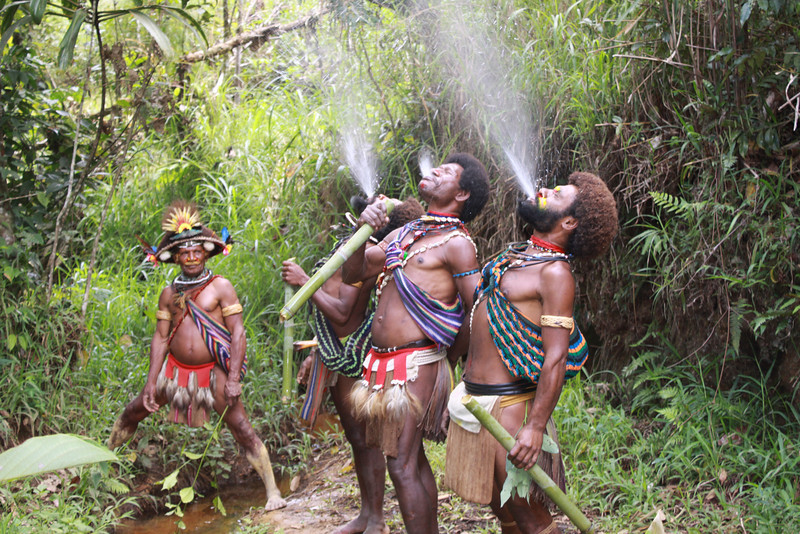 Huli wig school students spitting water to cleanse