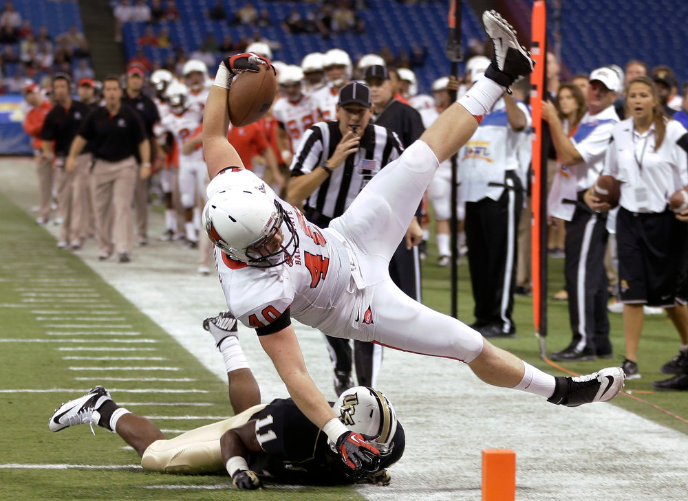 . Ball State tight end Dylan Curry (40) is upended by Central Florida linebacker Jonathan Davis (11) during the first quarter of the Beef \'O\' Brady\'s Bowl NCAA college football game Friday, Dec. 21, 2012, in St Petersburg, Fla. (AP Photo/Chris O\'Meara)