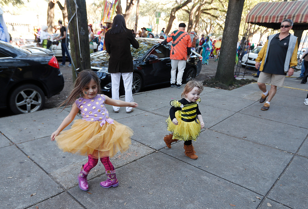 . Children dance on the sidewalk as the Society de Sainte Anne parade passes by, on Mardi Gras day in New Orleans, Tuesday, Feb. 13, 2018. (AP Photo/Gerald Herbert)
