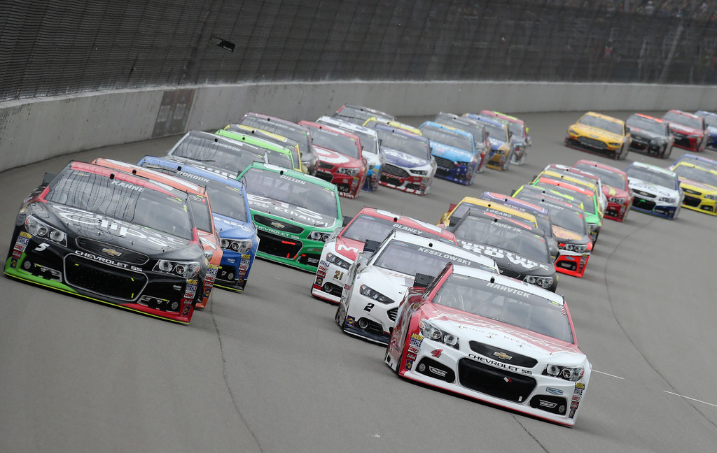 . Kasey Kahne, left, and Kevin Harvick lead the field through the first turn during the NASCAR Sprint Cup series auto race at Michigan International Speedway, Sunday, June 14, 2015, in Brooklyn, Mich. (AP Photo/Bob Brodbeck)