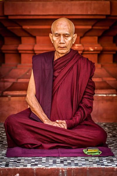 YANGON, MYANMAR - JANUARY 3, 2014: Ascetic Buddhist monk meditating in Shwedagon Paya pagoda