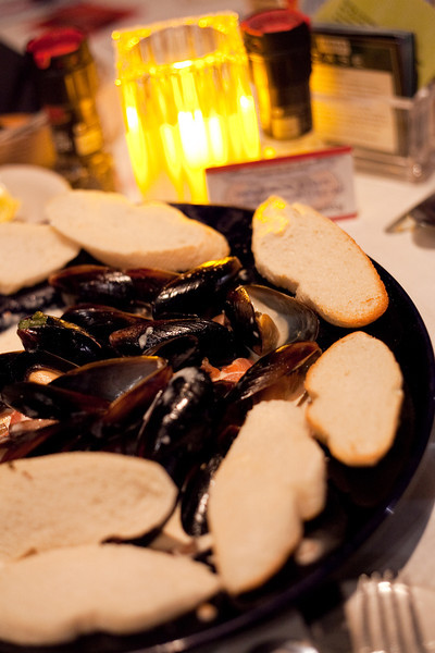 Food for Thought, What Big Mussels You Have! A heaping bowl of black shelled mussels steamed in white wine and finished with a basil garlic cream sauce and served with toasted crostinis for dipping the wonderful juices.