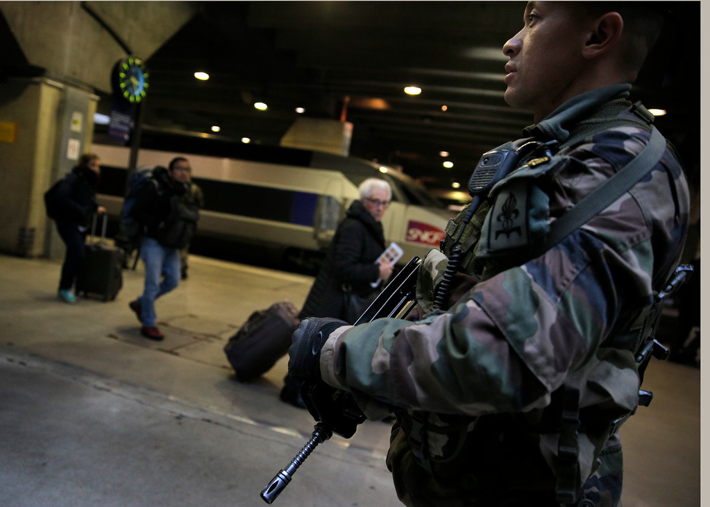 . A French soldier patrols at the Montparnasse railway station in Paris, France, Wednesday, Jan. 7, 2015. France reinforced security at houses of worship, stores, media offices and transportation after masked gunmen stormed the offices of a French satirical newspaper Wednesday, killing at least 11 people before escaping, police and a witness said. The weekly has previously drawn condemnation from Muslims. (AP Photo/Christophe Ena)