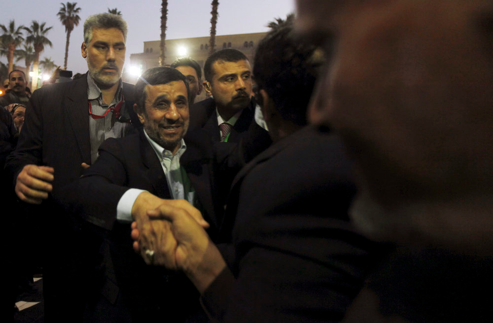 Description of . Iran's President Mahmoud Ahmadinejad (2nd L) shakes hands with people as he arrives in front of the Al-Hussein mosque, named after Prophet Mohammed's grandson Hussein ibn Ali, in old Cairo February 5, 2013. Ahmadinejad was both kissed and scolded on Tuesday when he began the first visit to Egypt by an Iranian president since Tehran's 1979 Islamic revolution. The trip was meant to underline a thaw in relations since Egyptians elected an Islamist head of state, President Mohamed Mursi, last June. But it also highlighted deep theological and geopolitical differences. REUTERS/Amr Abdallah Dalsh