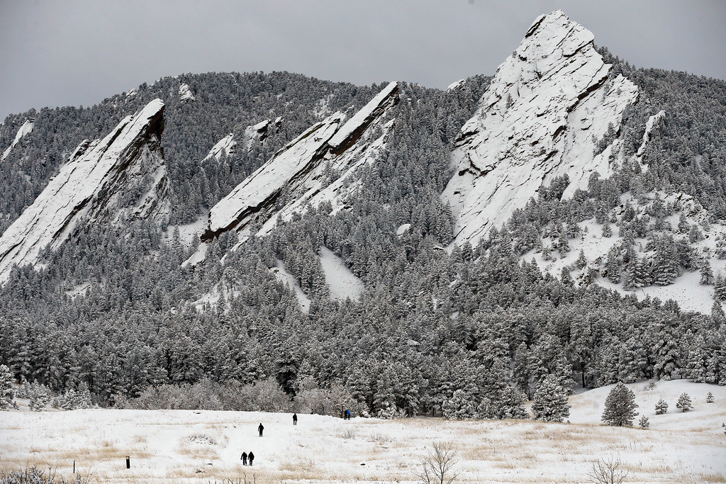 . Hikers walk up a snowy trail in Chautauqua Park, in Boulder, Colo., Thursday, Jan. 5, 2017. A winter storm dropped several feet of snow in the Colorado high country, and over a foot in Front Range communities. (AP Photo/Brennan Linsley)