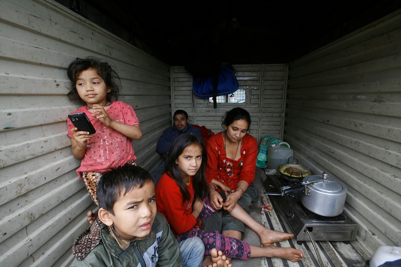 . Nepalese rest inside a van where they have taken shelter as it is considered safer in cars than inside houses with repeated aftershocks, in Kathmandu, Nepal, Sunday, April 26, 2015. Sleeping in the streets and shell-shocked, Nepalese cremated the dead and dug through rubble for the missing Sunday even as the worst of the aftershocks, magnitude 6.7, pummeled the capital city. (AP Photo/Bikram Rai)
