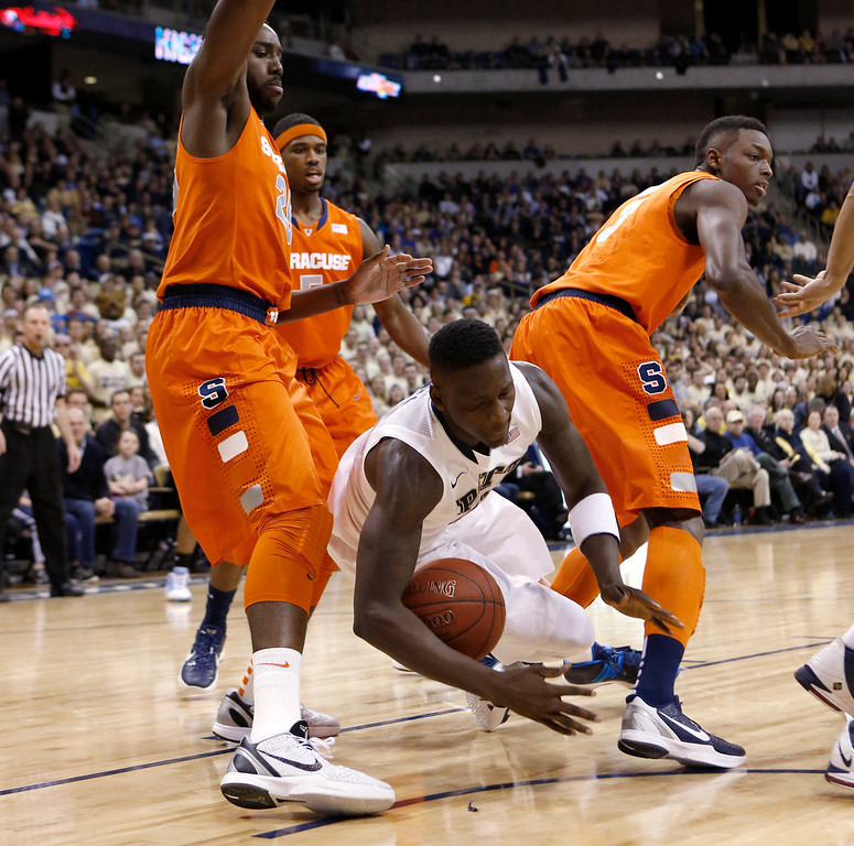 . Pittsburgh\'s Talib Zanna, center, tumbles between Syracuse\'s Rakeem Christmas, left, and Jerami Grant, right, during the first half of an NCAA college basketball game Wednesday, Feb. 12, 2014, in Pittsburgh. (AP Photo/Keith Srakocic)