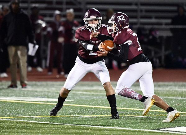 11/15/2019 Mike Orazzi rBristol Central's Victor Rosa (2) hands off to Shawn Rodriguez (32) during Friday night's football game with Conard High School at BC.