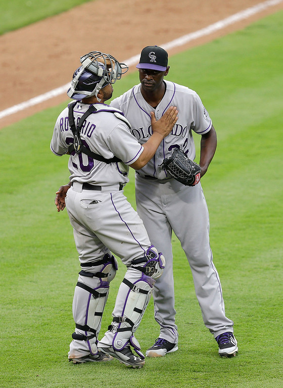 . Closer LaTroy Hawkins #32 of the Colorado Rockies (right) is congratulated by catcher Wilin Rosario #20 after the game against the Atlanta Braves at Turner Field on May 24, 2014 in Atlanta, Georgia.  The Rockies beat the Braves 3-1.  (Photo by Mike Zarrilli/Getty Images)