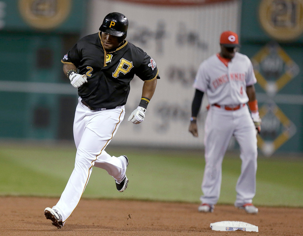 . Pittsburgh Pirates\' Marlon Byrd (2) rounds the bases past Cincinnati Reds second baseman Brandon Phillips after hitting a home run in the second inning of the NL wild-card playoff baseball game Tuesday, Oct. 1, 2013, in Pittsburgh. (AP Photo/Gene J. Puskar)