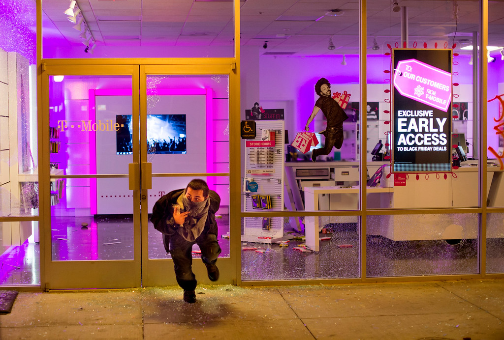 . A man leaves a looted T-Mobile store in Oakland, Calif., on Tuesday, Nov. 25, 2014, a day after the announcement that a grand jury decided not to indict Ferguson police officer Darren Wilson in the fatal shooting of Michael Brown. Protesters briefly shut down two major freeways, vandalized police cars and looted businesses in downtown Oakland, smashing windows at cell phone stores, car dealerships, restaurants and convenience stores on a second night of protests. (AP Photo/Noah Berger)