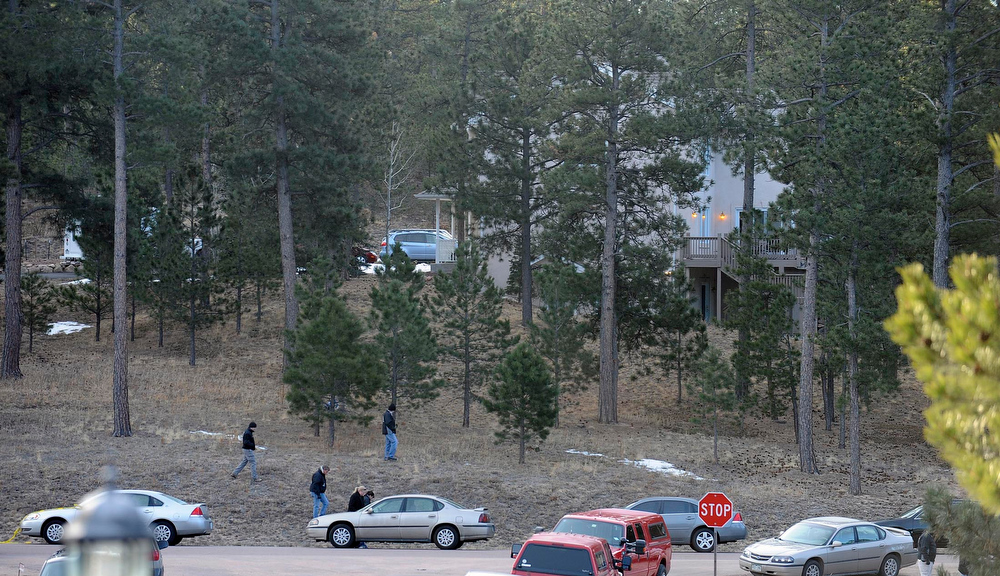 . Investigators search the area surrounding the home of Tom Clements, executive director of the Colorado Dept. of Corrections on Colonial Park Dr. east of Monument Wednesday morning. (Photo By Steve Nehf / The Denver Post)