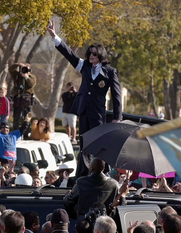 """. Michael Jackson flashes the \""""V\"""" sign to the fans from atop his limousine after his arraignment on child molestation charges at the courthouse in Santa Maria, Calif., Friday morning, Jan. 16, 2004.  (AP Photo/Mark J. Terrill)"""