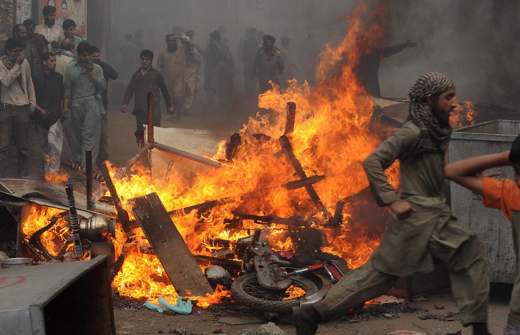 . Angry Pakistani demonstrators gather around burning Christian\'s belongings during a protest over a blasphemy row in a Christian neighborhood in Badami Bagh area of Lahore on March 9, 2013. Thousands of angry protestors on March 9 set ablaze more than 100 houses of Pakistani Christians over a blasphemy row in the eastern city of Lahore, officials said. Over 3,000 Muslim protestors turned violent over derogatory remarks allegedly made by a young Christian, Sawan Masih, 28 against Prophet Muhammad in a Christian neighboorhood in Badami Bagh area. Arif Ali/AFP/Getty Images