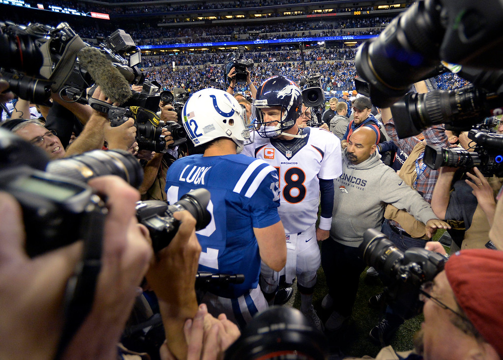 . Denver Broncos quarterback Peyton Manning (18) meets with Indianapolis Colts quarterback Andrew Luck (12) after the game October 20, 2013 at Lucas Oil Field. Photo by John Leyba/The Denver Post)