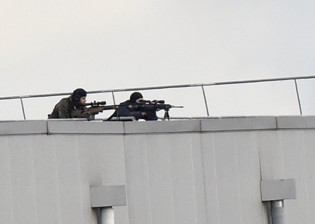 . Police marksmen take up a position on a roof in Dammartin-en-Goele, north-east of Paris, where two brothers suspected of slaughtering 12 people in an Islamist attack on French satirical newspaper Charlie Hebdo held one person hostage as police cornered the gunmen, on January 9, 2015. The hostage drama unfolded at a printing business in the small town of Dammartin-en-Goele, only 12 kilometers (seven miles) from Paris\'s main Charles de Gaulle airport, police sources said. AFP PHOTO / DOMINIQUE  FAGET/AFP/Getty Images