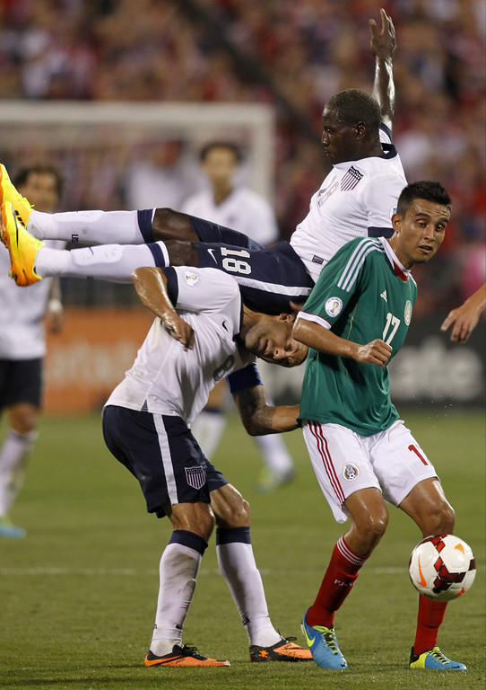 . Eddie Johnson (C) of USA collides with teammate Clint Dempsey (L) as they work for the ball against Jesus Zavala (R) of Mexico during the second half of their Brazil 2014 FIFA World Cup qualifier at Columbus Crew Stadium in Columbus, Ohio, September 10, 2013.  USA won 2-0. AFP PHOTO / PAUL VERNONPaul VERNON/AFP/Getty Images