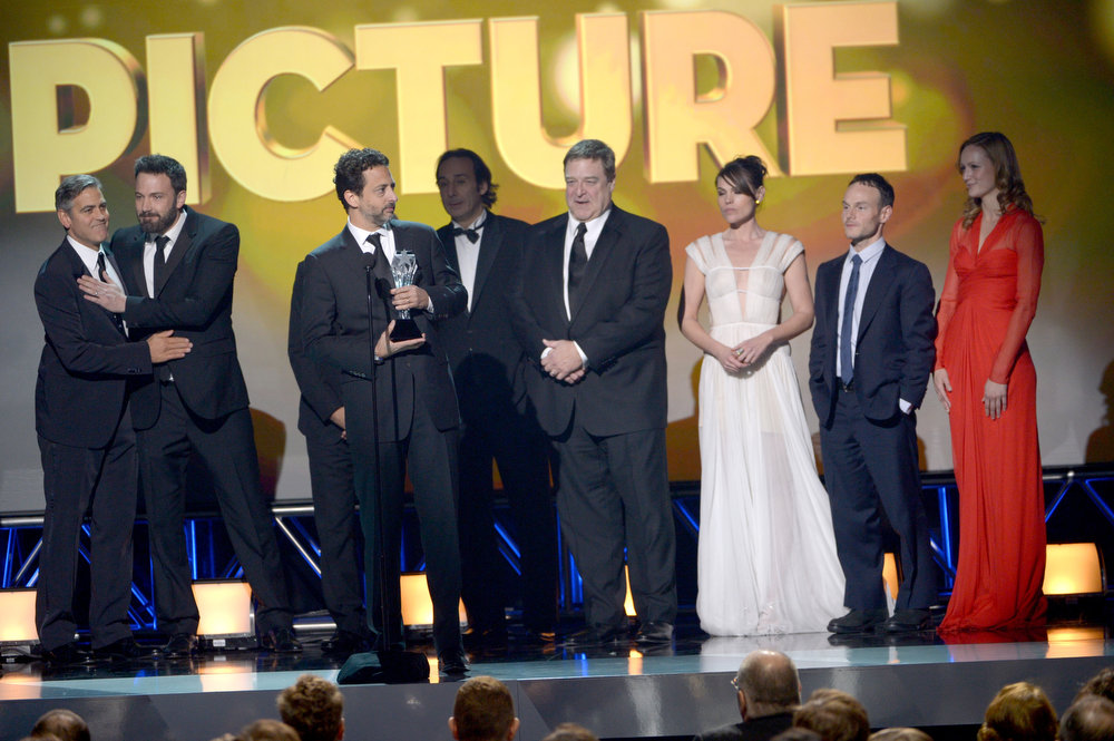 ". (L-R) Producer George Clooney, Actor/Producer/Director Ben Affleck, Producer Grant Heslov, Composer Alexandre Desplat, actor John Goodman, actress Clea DuVall, writer Chris Terrio and actress Kerry Bishe, accept the Best Picture Award for ""Argo\"" onstage at the 18th Annual Critics\' Choice Movie Awards held at Barker Hangar on January 10, 2013 in Santa Monica, California.  (Photo by Kevin Winter/Getty Images)"