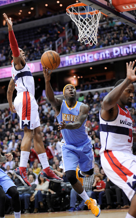 . Denver Nuggets guard Ty Lawson, center, takes a shot between Washington Wizards\' Bradley Beal, left, and Martell Webster during the first half of an NBA basketball game, Friday, Feb. 22, 2013, in Washington. (AP Photo/Nick Wass)
