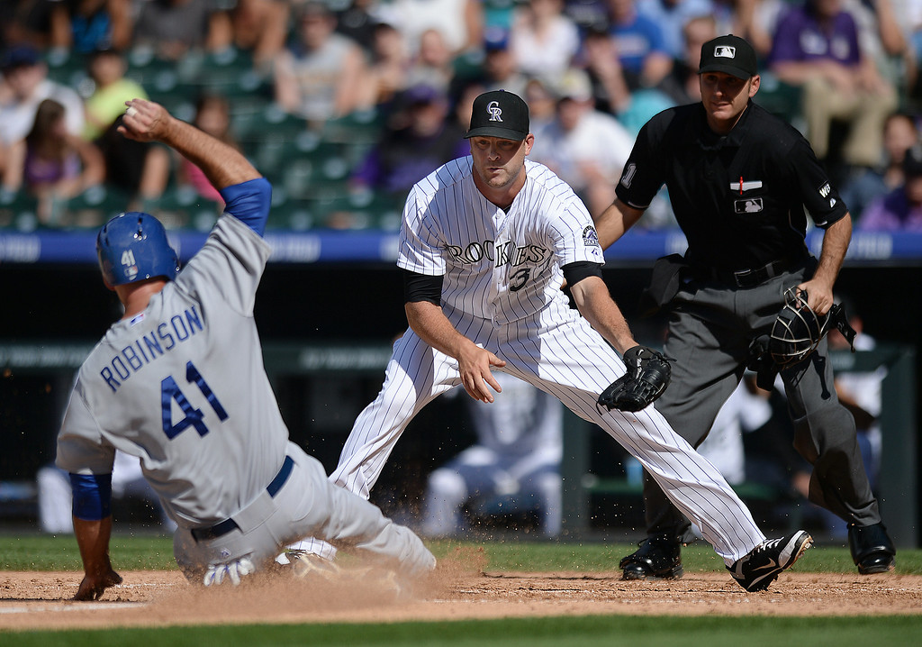 . DENVER, CO - JULY 5:  Dodgers baserunner Clint Robinson scored from third base after Rockies reliever Nick Massett threw a wild pitch and wasn\'t able to cover home plate in time. The Colorado Rockies defeated the Los Angeles Dodgers 8-7 at Coors Field Saturday afternoon, July 5, 2014.  Photo by Karl Gehring/The Denver Post