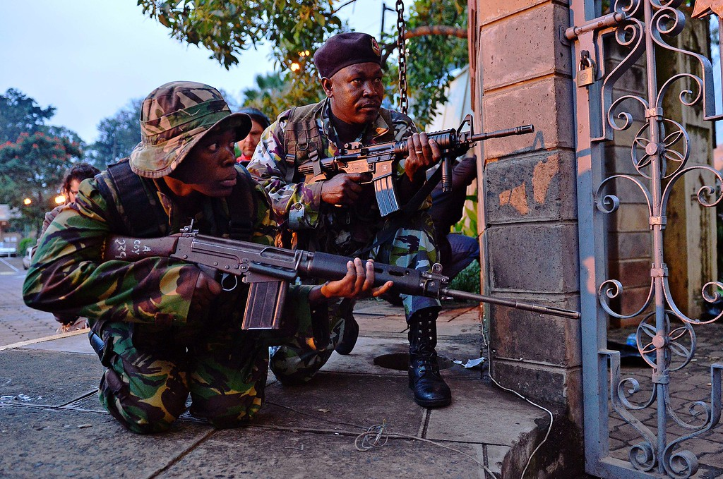 . Kenyan soldiers take cover after heavy gunfire near Westgate mall in Nairobi on September 23, 2013. Kenyan Defense troops remain inside the mall, in a standoff with Somali militants after they laid siege to the shopping centre shooting and throwing grenades as they entered. Somali Shebab militants on September 23 threatened to kill hostages they are holding in the Nairobi shopping mall as Kenyan troops move to end their siege. AFP PHOTO / CARL DE SOUZA/AFP/Getty Images