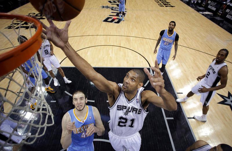 . San Antonio Spurs\' Tim Duncan (21) grabs a rebound over Denver Nuggets\' Kosta Koufos (41) during the first half of an NBA basketball game, Wednesday, March 27, 2013, in San Antonio. (AP Photo/Eric Gay)