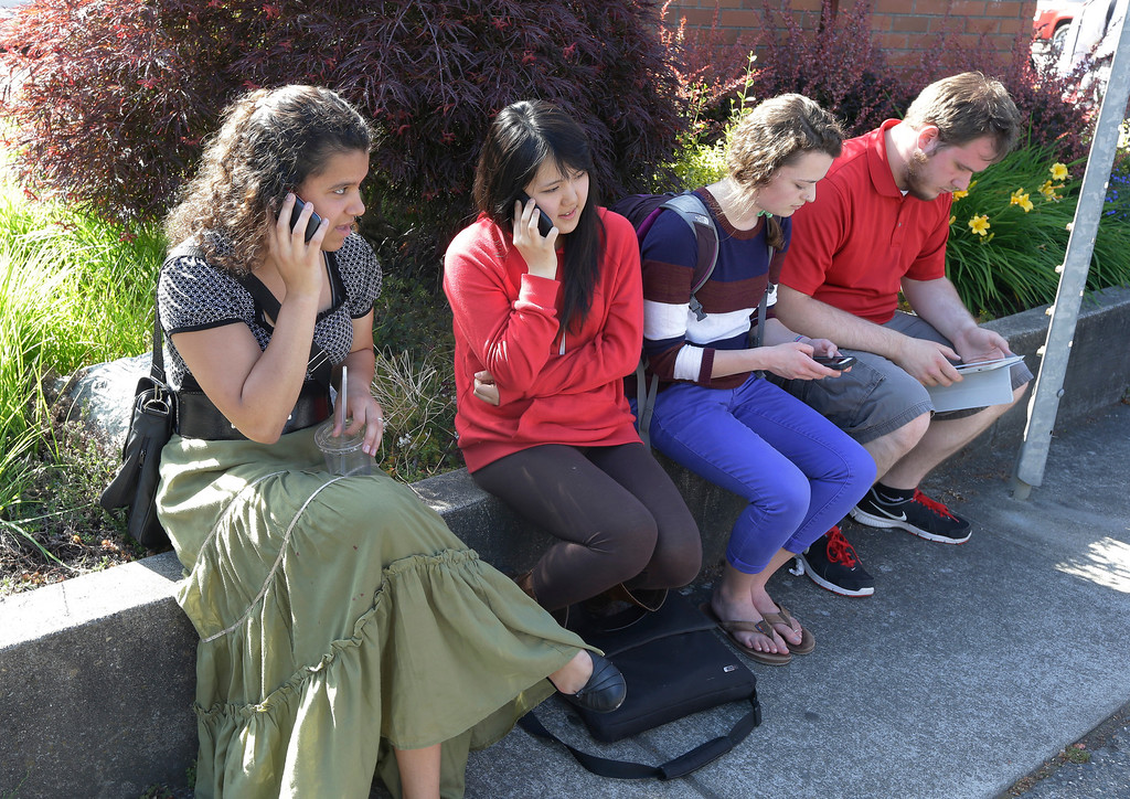 . Students use cell phones near the scene of a shooting Thursday, June 5, 2014 at Seattle Pacific University in Seattle. A lone gunman armed with a shotgun opened fire Thursday in a building at the small Seattle university, killing one person before he was subdued by a student as he tried to reload, police said. Police say the student building monitor disarmed the gunman and several other students held him until police arrived at the Otto Miller building. (AP Photo/Ted S. Warren)