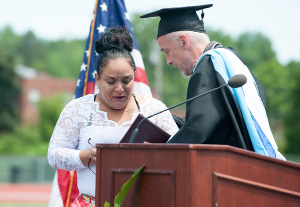 06/19/18 Wesley Bunnell | Staff Betty Velez, mother of NBHS Satellite Careers Academy student Moses Negron who passed away during an auto accident during the school year, accepts an honorary diploma in her sons name from Principal of Satellite Careers Academy Michael Foran. New Britain High School held their graduation exercises at Veterans' Memorial Stadium at Willow Brook Park on Tuesday morning.