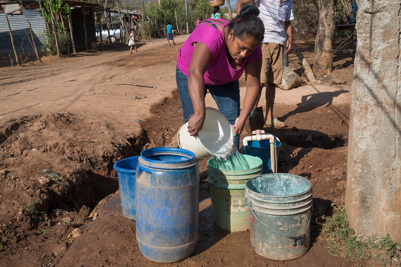 Woman draws water from public spigot before running water was provided to houses.