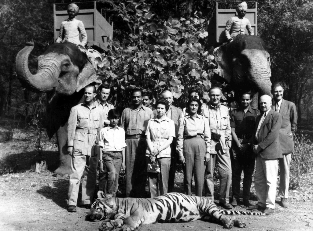 . Britain\'s Queen Elizabeth II and Prince Philip, stand with their hosts Maharajah and Maharanee of Jaipur, in the forests of Rajsthan, India, Jan. 24, 1961. From left; Prince Philip, unknown, unknown child, Maharajah of Jaipur, Queen, Maharanee Gayatri Devi, rest are unamed. The tiger in the foreground was shot by Prince Philip and the elephants used in the hunt are seen at the back. (AP Photo)