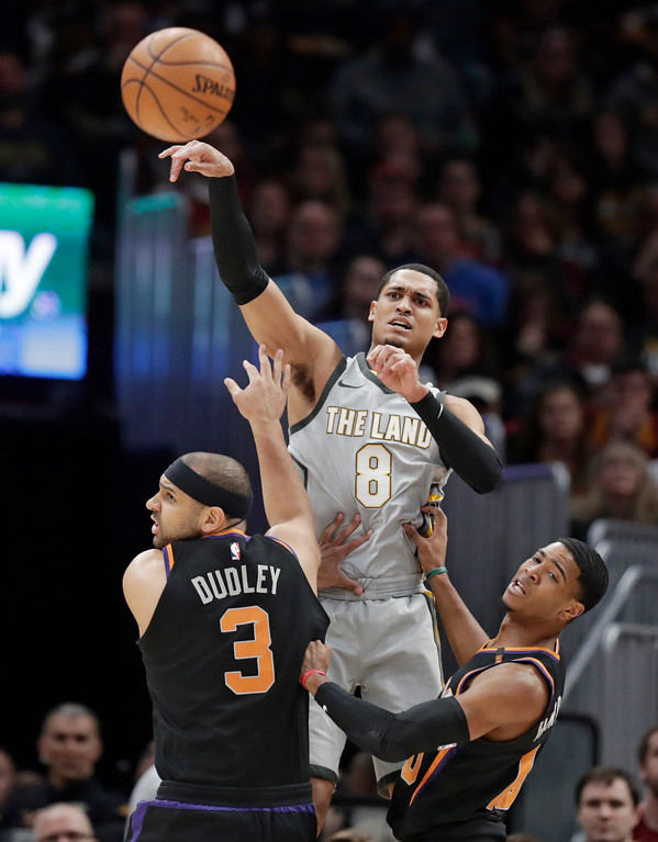 . Cleveland Cavaliers\' Jordan Clarkson (8) passes the ball over Phoenix Suns\' Jared Dudley (3) and Shaquille Harrison (10) during the first half of an NBA basketball game Friday, March 23, 2018, in Cleveland. (AP Photo/Tony Dejak)