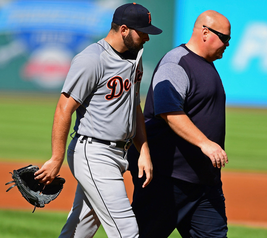 . Detroit Tigers starting pitcher Michael Fulmer, left, walks to the dugout with a trainer in the first inning of a baseball game against the Cleveland Indians, Saturday, Sept.15, 2018, in Cleveland. (AP Photo/David Dermer)