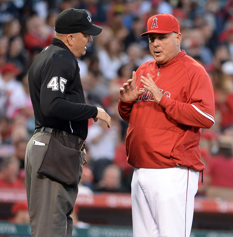 . Los Angeles Angels manager Mike Scioscia talks with home plate umpire Jeff Nelson (45) in the first inning of a baseball game at Anaheim Stadium in Anaheim, Calif., on Wednesday, May 7, 2014.  (Keith Birmingham Pasadena Star-News)