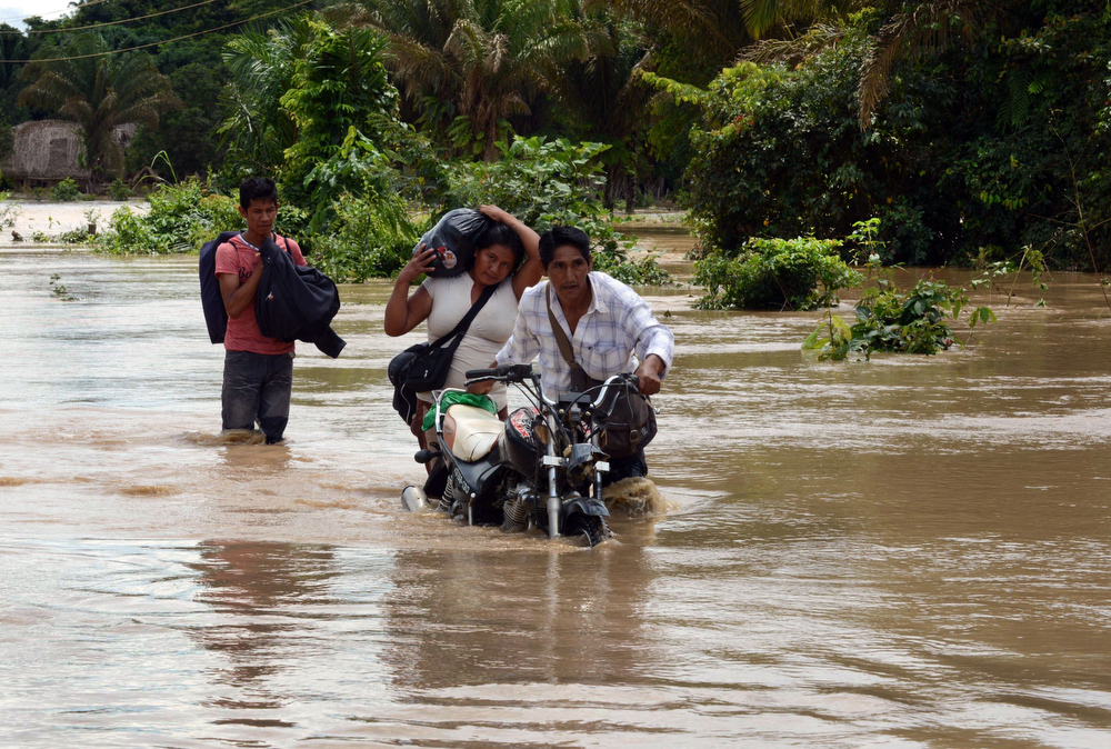 Description of . A family wades through a flooded highway, following the overflowing of the Beni river and heavy rains hitting the country, in Reyes, department of Beni, northeast Bolivia, on February 2, 2014. (AIZAR RALDES/AFP/Getty Images)